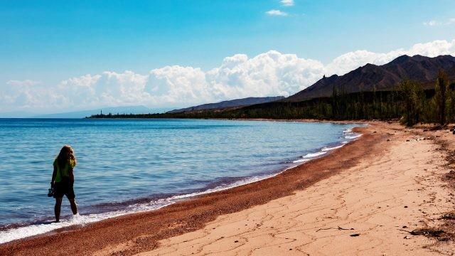 Девушка бредёт по берегу озера