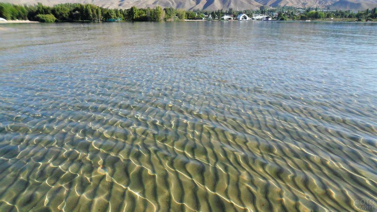 Песчаное дно виднеется сквозь прозрачную воду