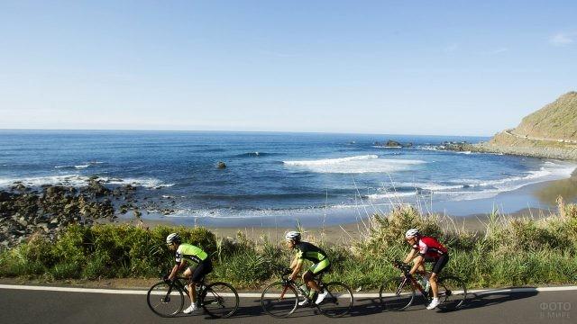 Трое велосипедистов мчатся по берегу Атлантического океана