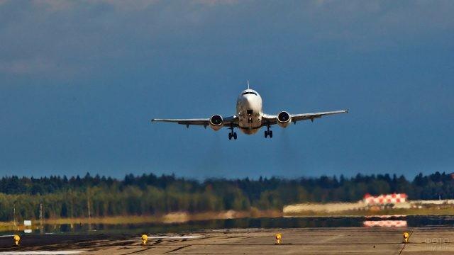 Самолёт над взлётно-посадочной полосой