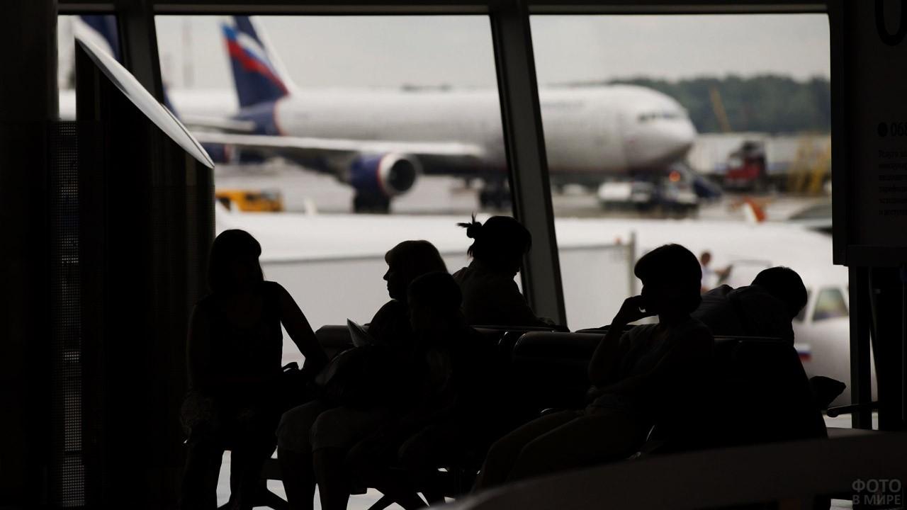 Силуэты пассажиров в зале ожидания
