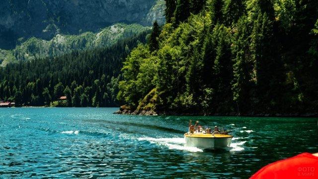 Туристы мчатся на катере по горному озеру