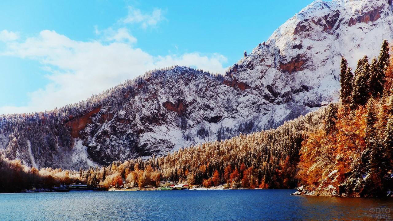 Заснеженный осенний лес на берегу горного озера