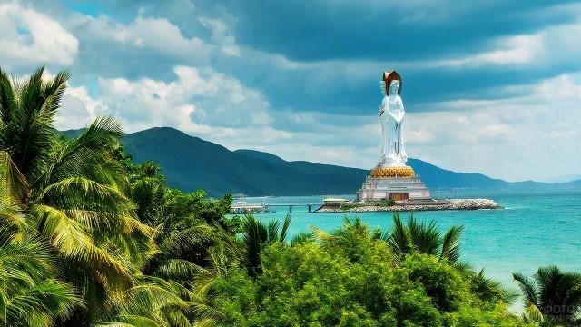 Буддистская статуя над тропической зеленью