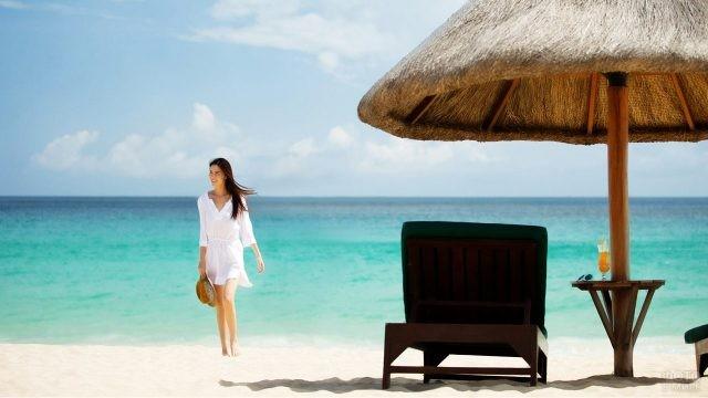 Девушка в белом на пляже с шезлонгами