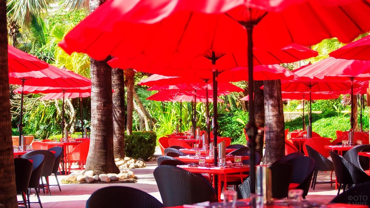 Столики уличного кафе под красными зонтиками