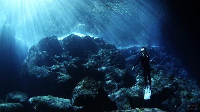 Аквалангист поднимается сквозь толщу воды