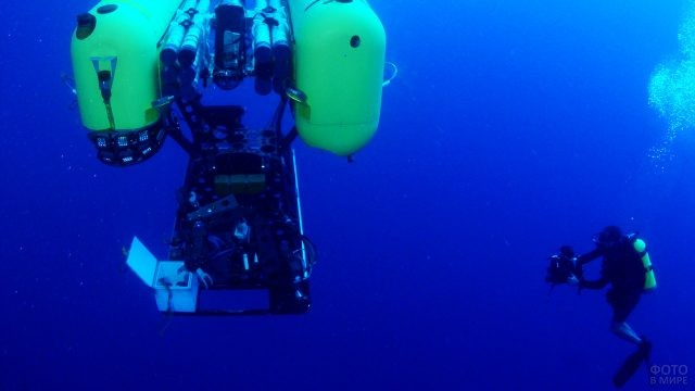 Океанолог с аквалангом работает вблизи подводного зонда