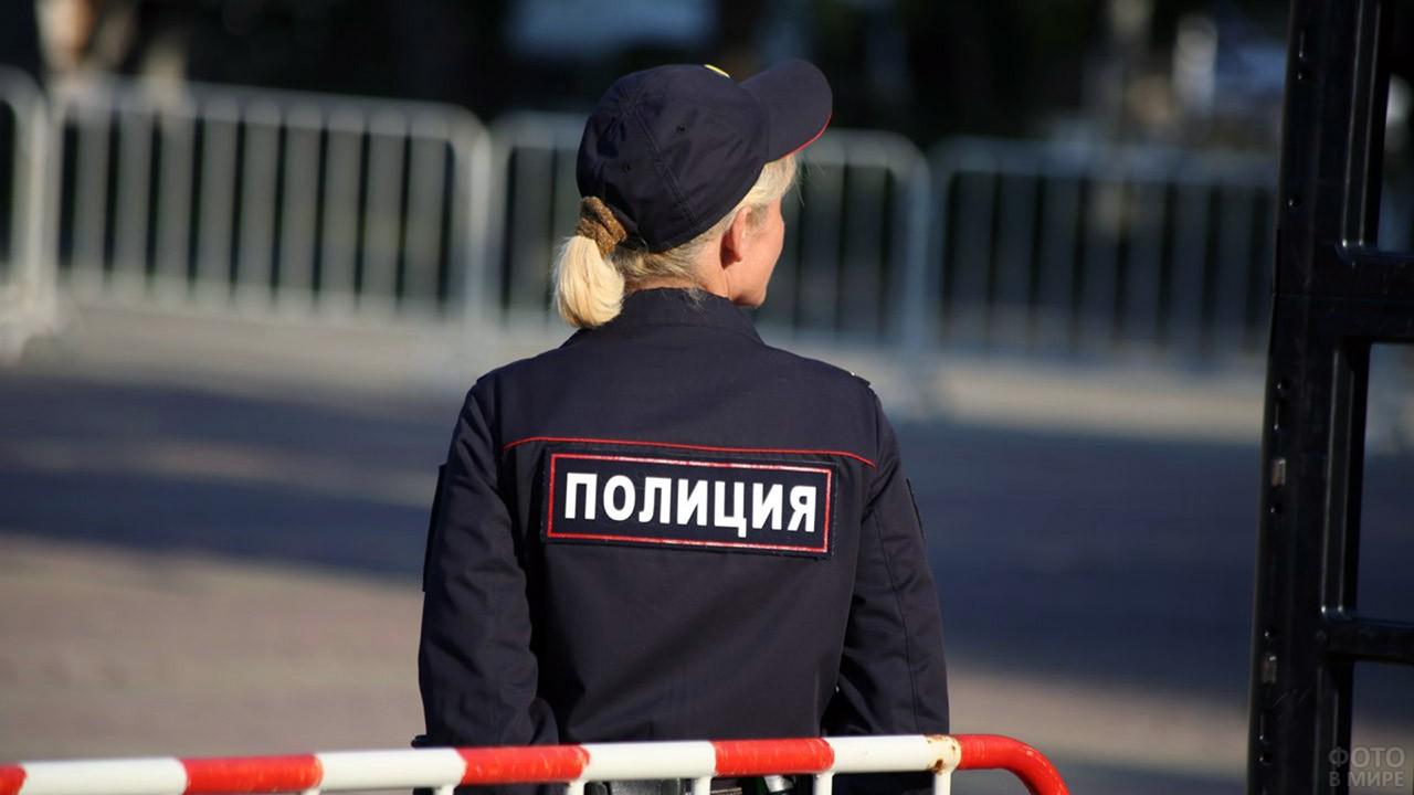 Надпись Полиция на спине девушки в форме