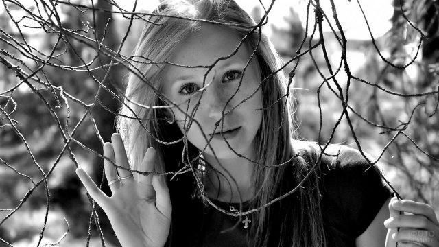 Девушка смотрит через сухие ветки деревьев