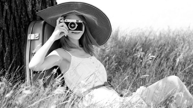 Девушка в шляпе у дерева фотографирует