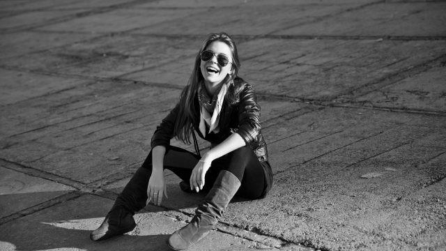 Девушка в солнцезащитных очках смеётся, сидя на бетоне