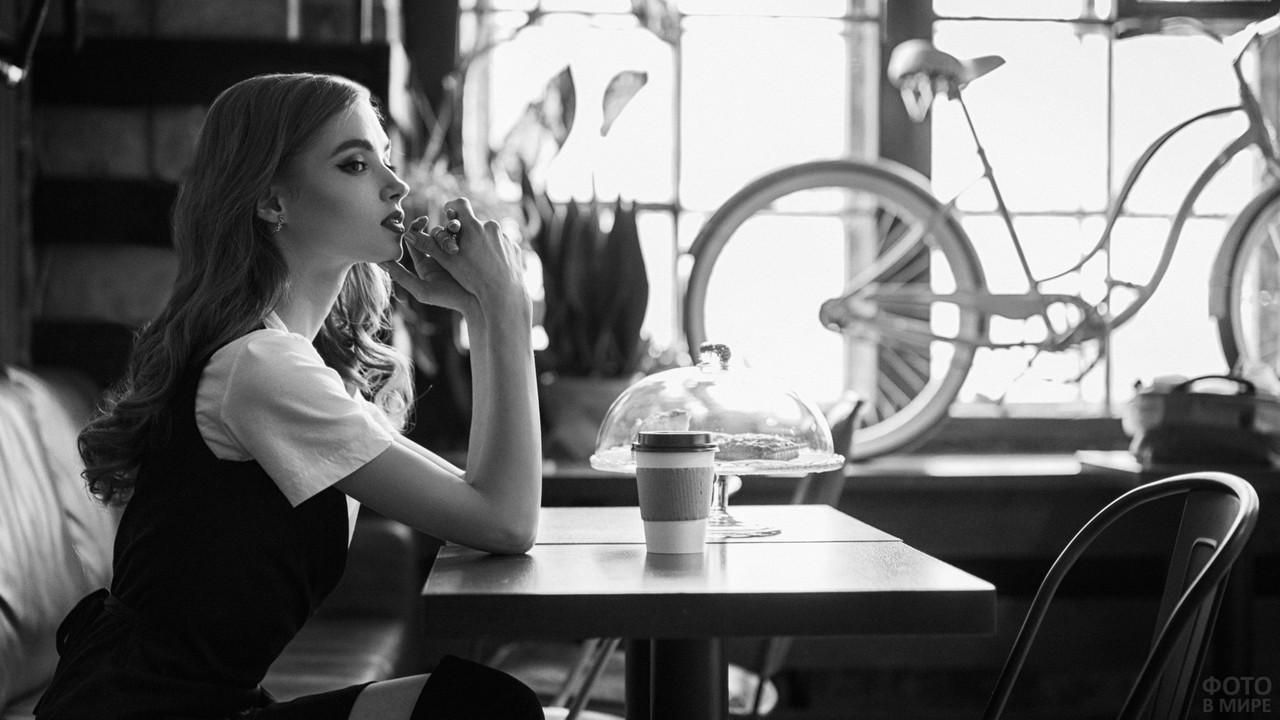 Красивая девушка ждёт заказ в кафе
