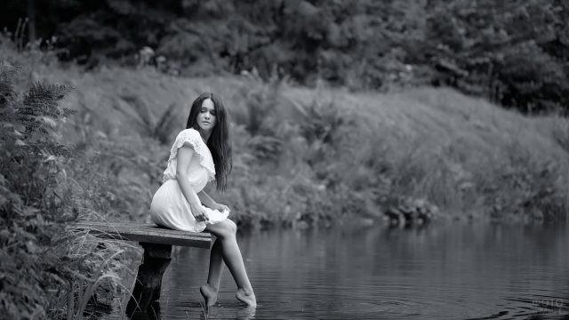 Милая девушка на мостике возле озера