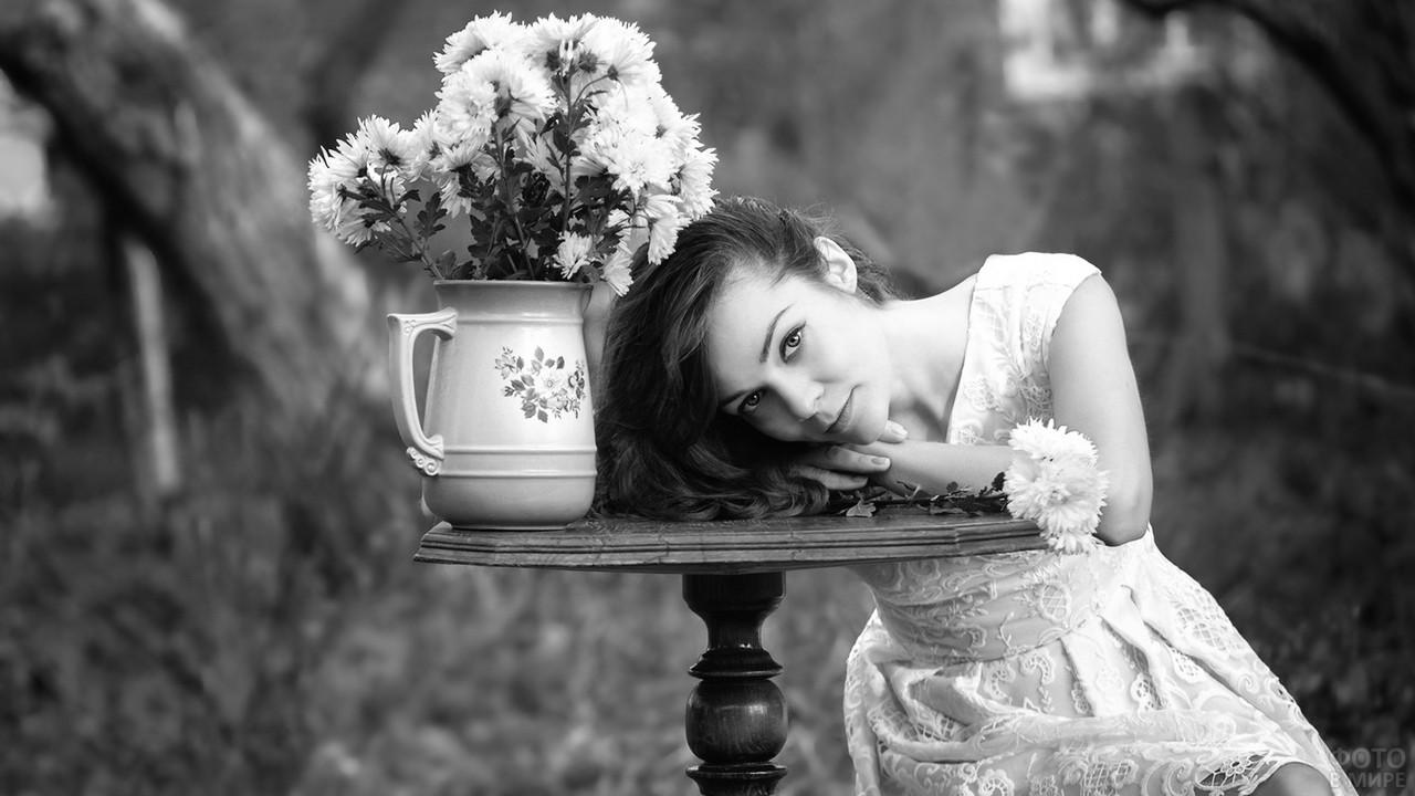 Нежная девушка за столиком с кувшином цветов