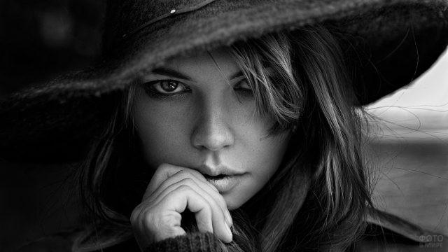 Серьёзная девушка в тёмной шляпе