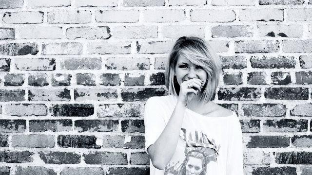 Смеющаяся девушка у кирпичной стены
