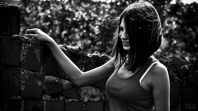 Улыбающаяся девушка положила руку на кирпичную стену