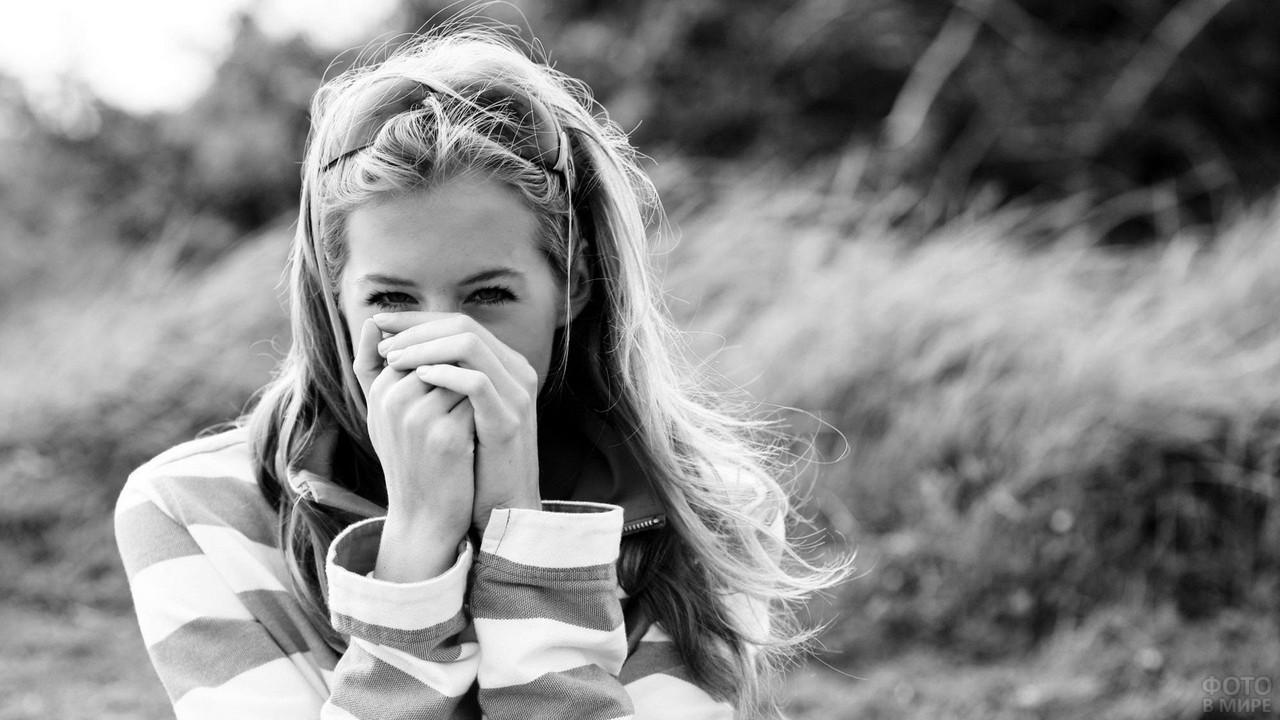 Улыбающаяся девушка прикрыла рот руками