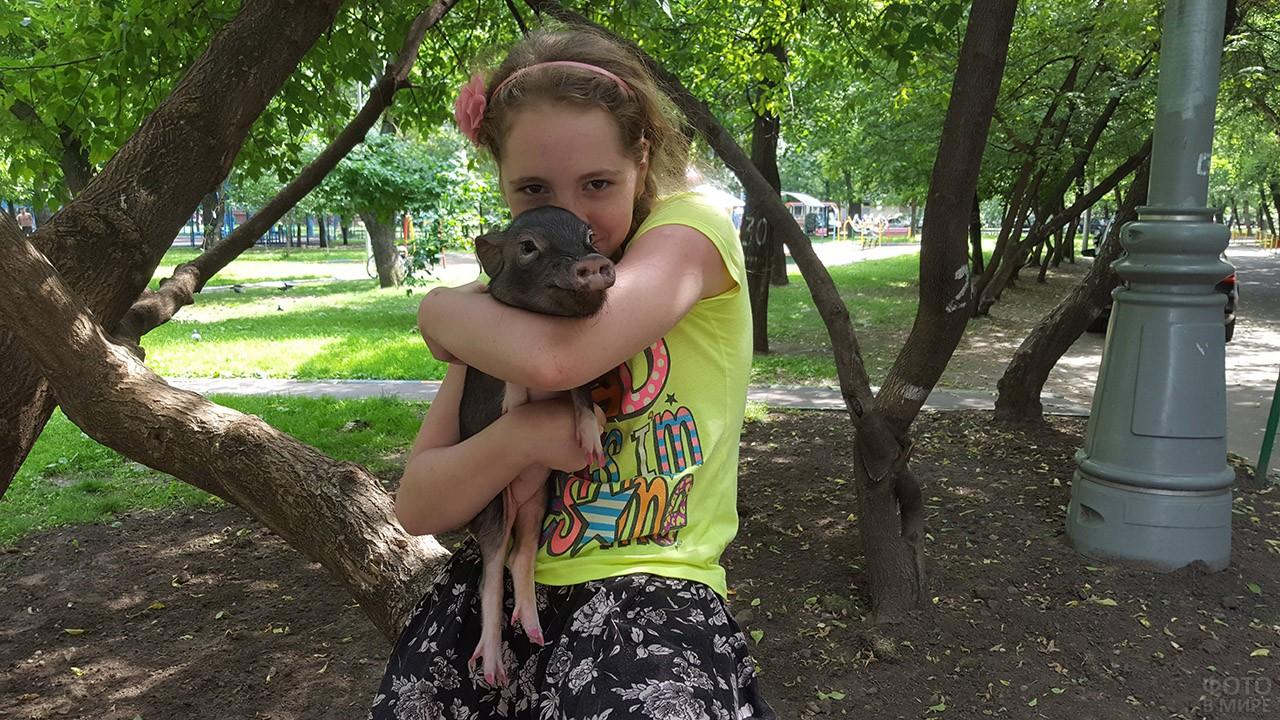 Девочка обнимает свинку