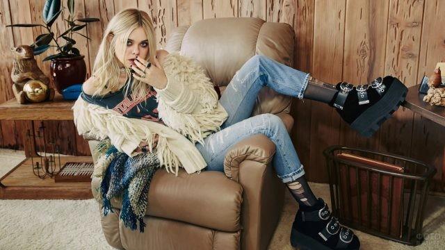 Блондинка сидит поперёк кресла