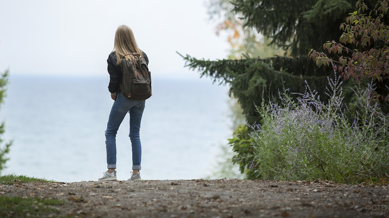 Девушка с рюкзаком смотрит на реку