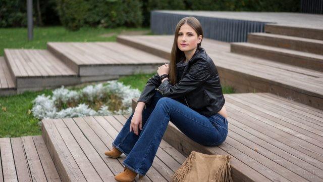 Девушка сидит на ступеньках