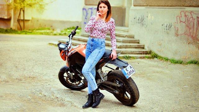 Девушка в джинсах около мотоцикла