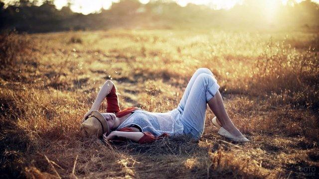 Девушка в шляпе лежит в поле