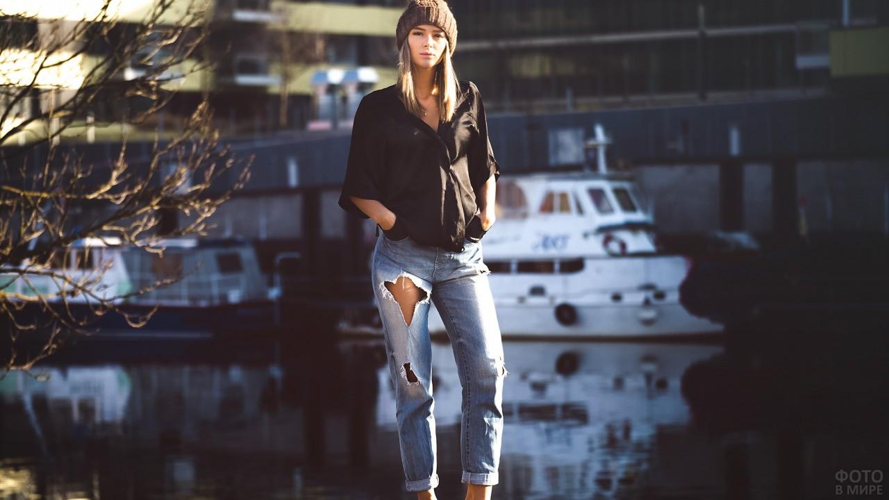 Модель в джинсах на фоне корабля
