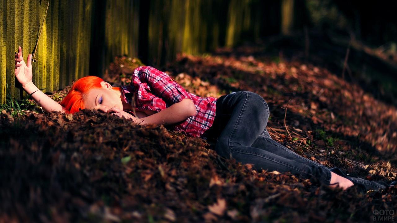 Девушка с красными волосами спит на земле