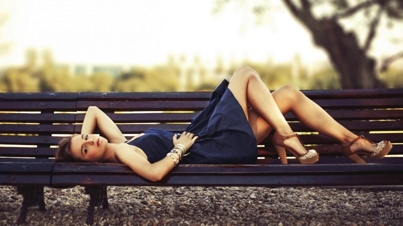 Девушка в коротком платье на скамейке летом