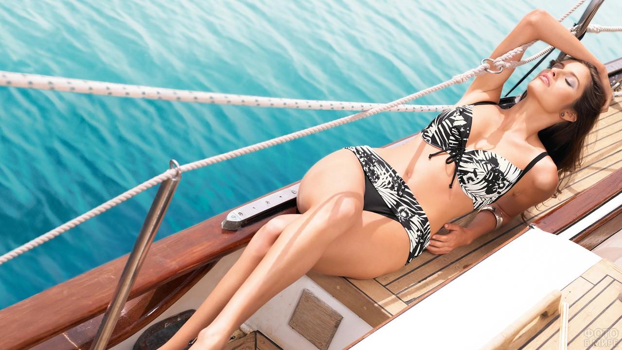 Девушка в купальнике лежит на яхте