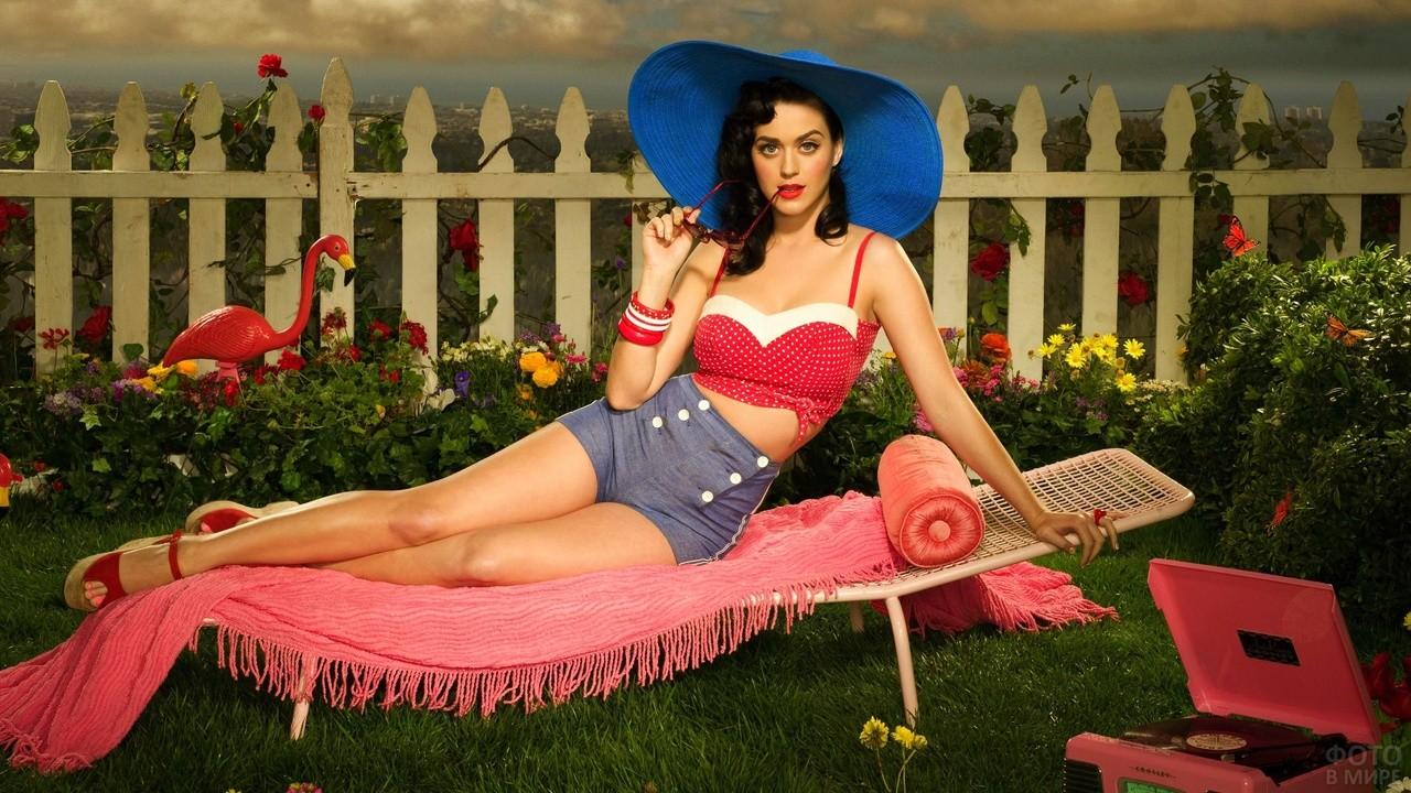 Девушка в синей широкополой шляпе на лежаке в саду
