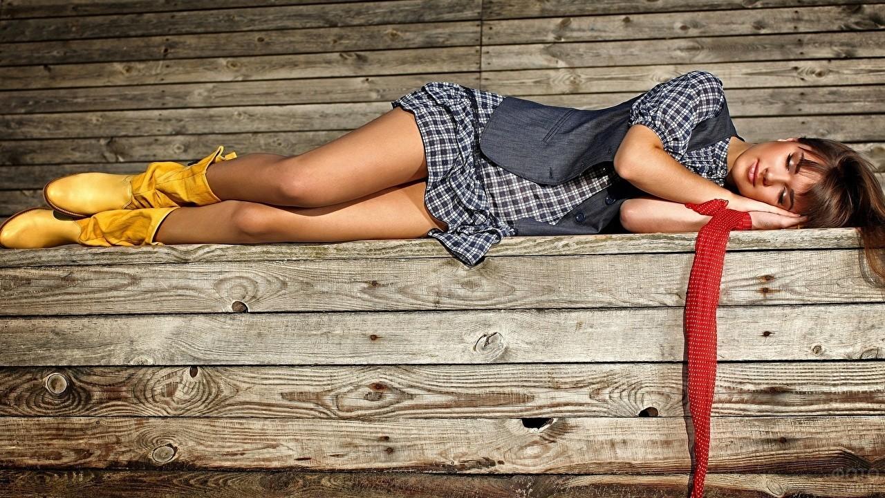 Девушка в жёлтых сапожках лежит на лавочке