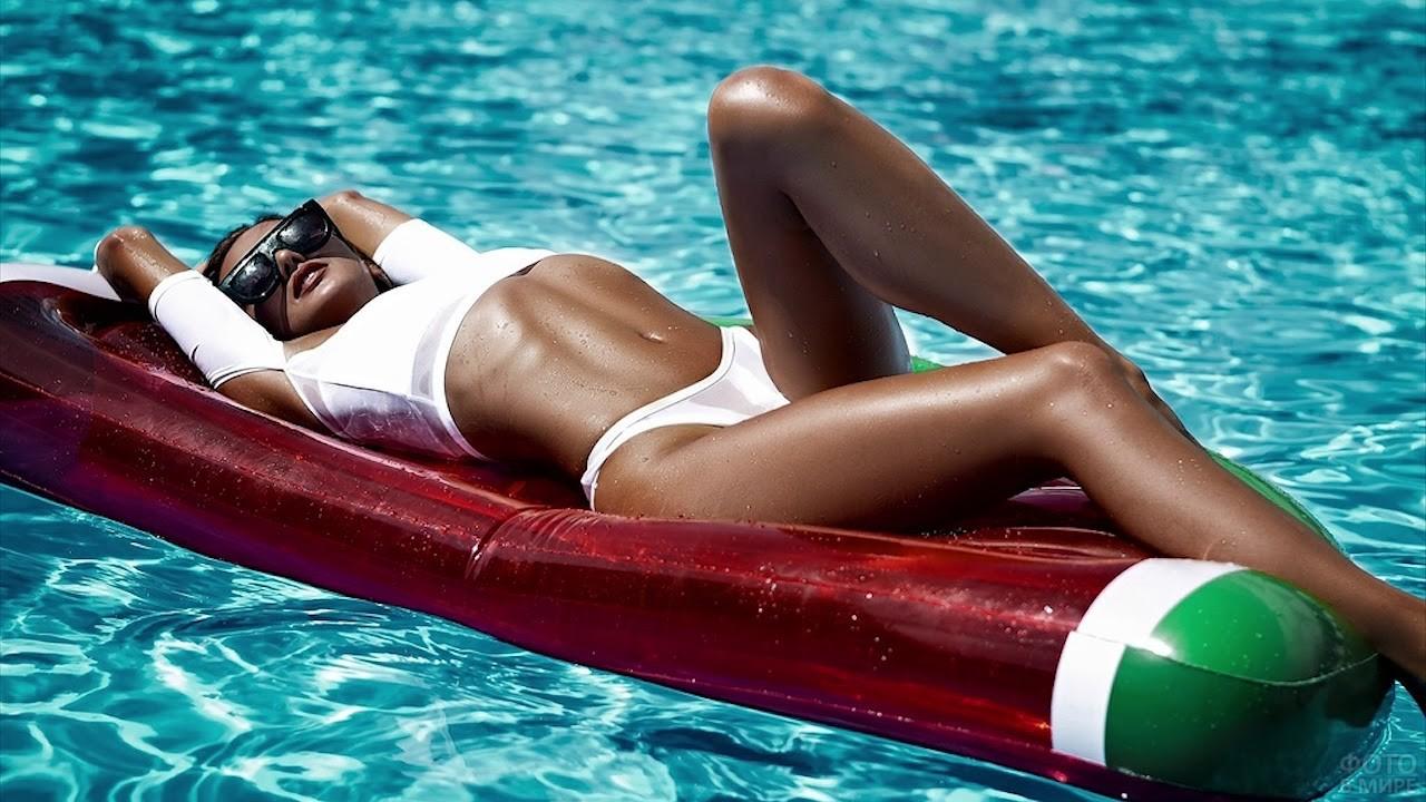 Загорелая девушка лежит на матрасе в воде