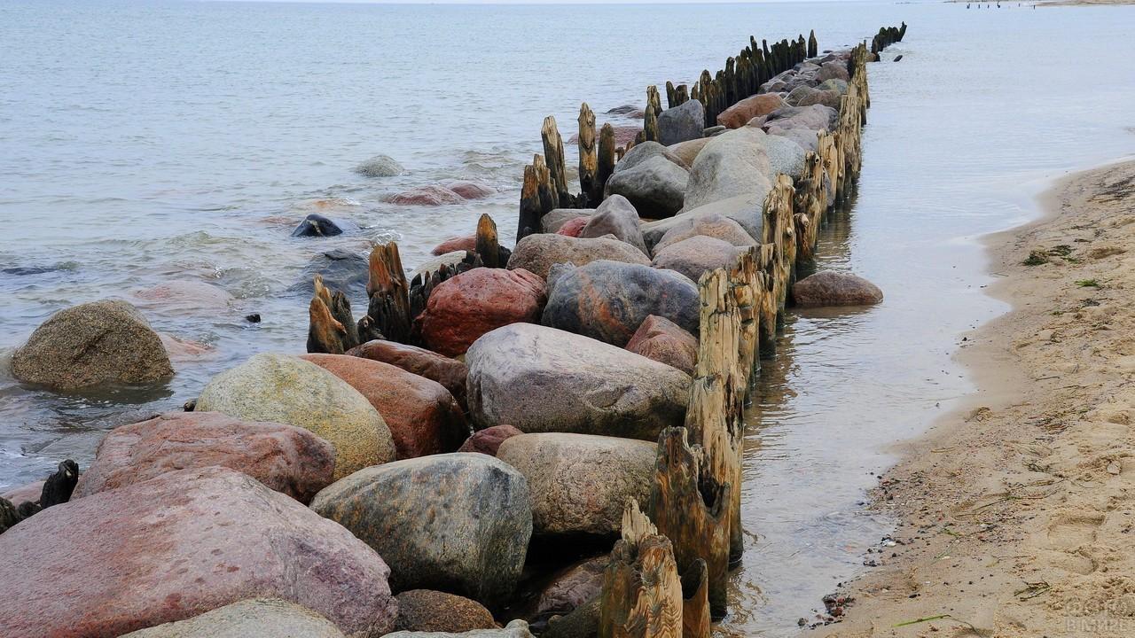 Волнорезы с камнями у берега