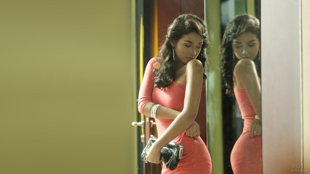 Девушка в розоватом платье смотрит на спину через зеркало