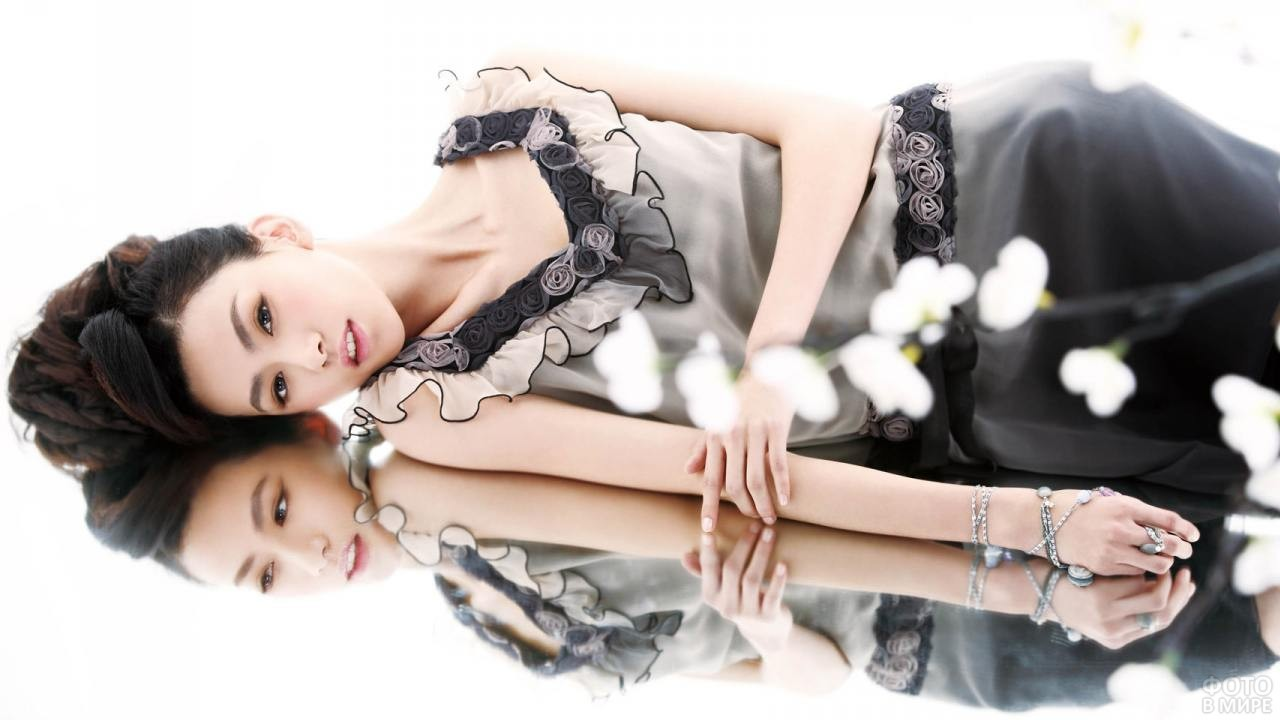 Японская девушка лежит на зеркале