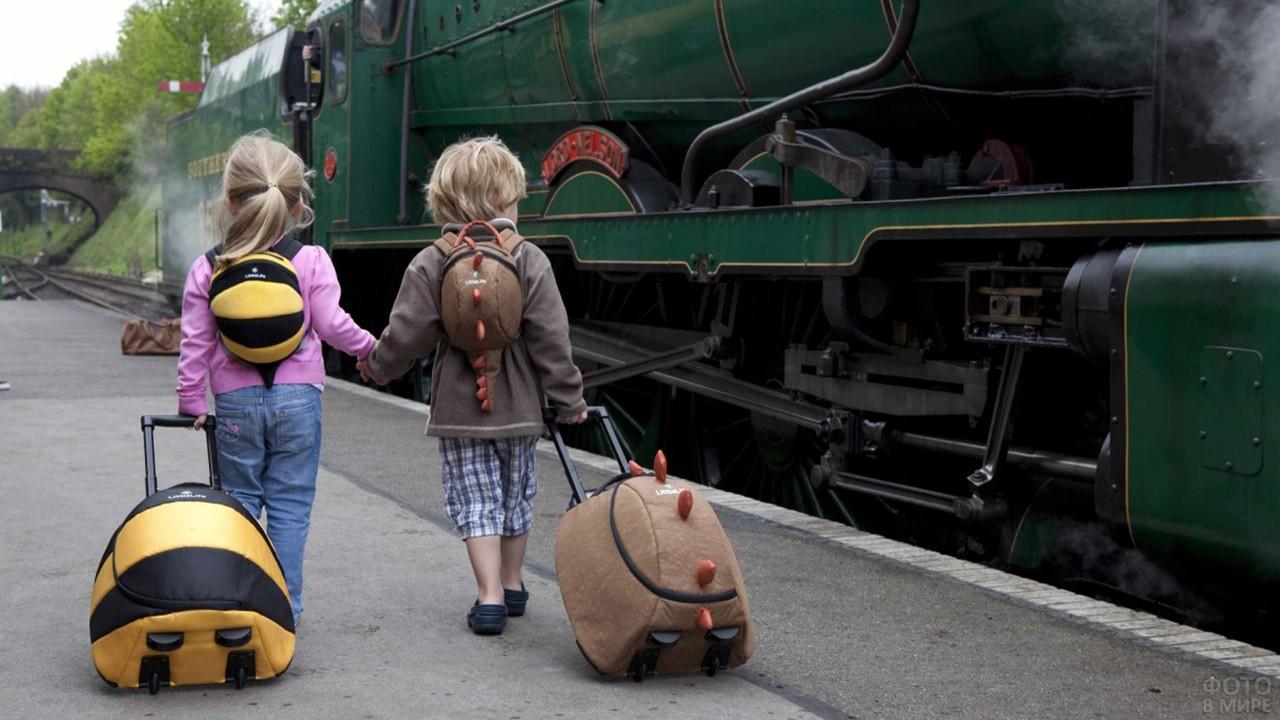 Малыши с чемоданами разглядывают паровоз