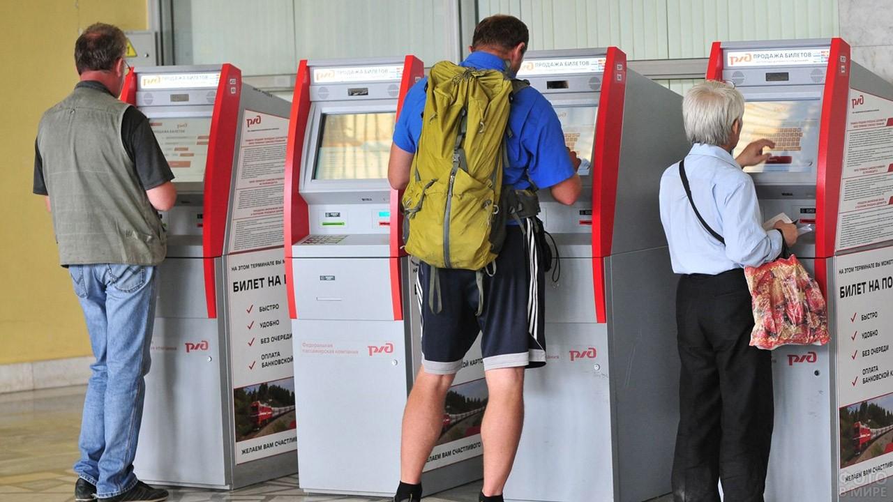Мужчины покупают билеты в терминалах самообслуживания