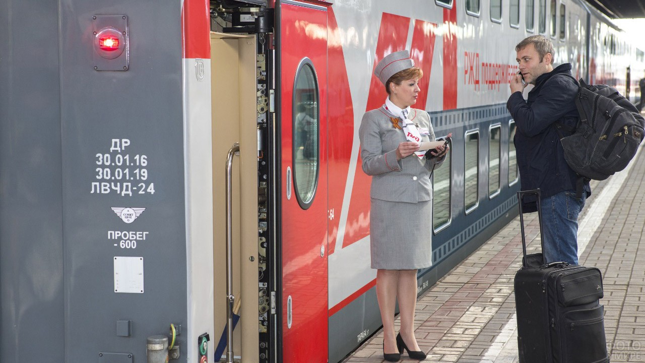 Проводник поезда проверяет билет у пассажира