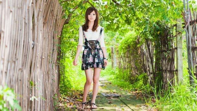 Азиатка в коротком сарафане стоит у плетня