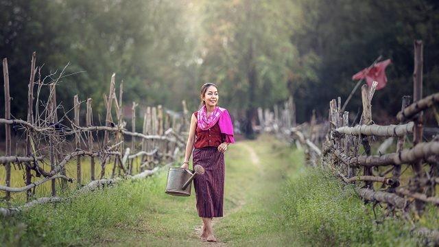 Деревенская девушка идёт с лейкой