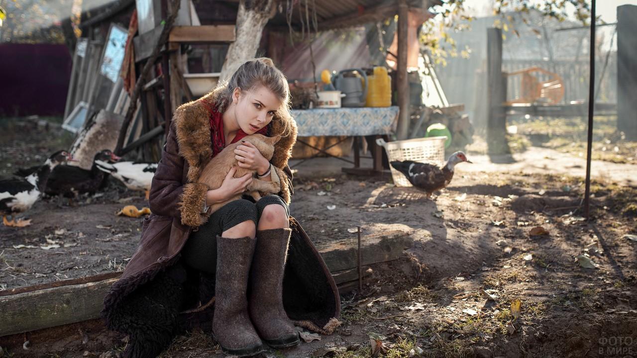 Деревенская девушка в валенках и котом в руках