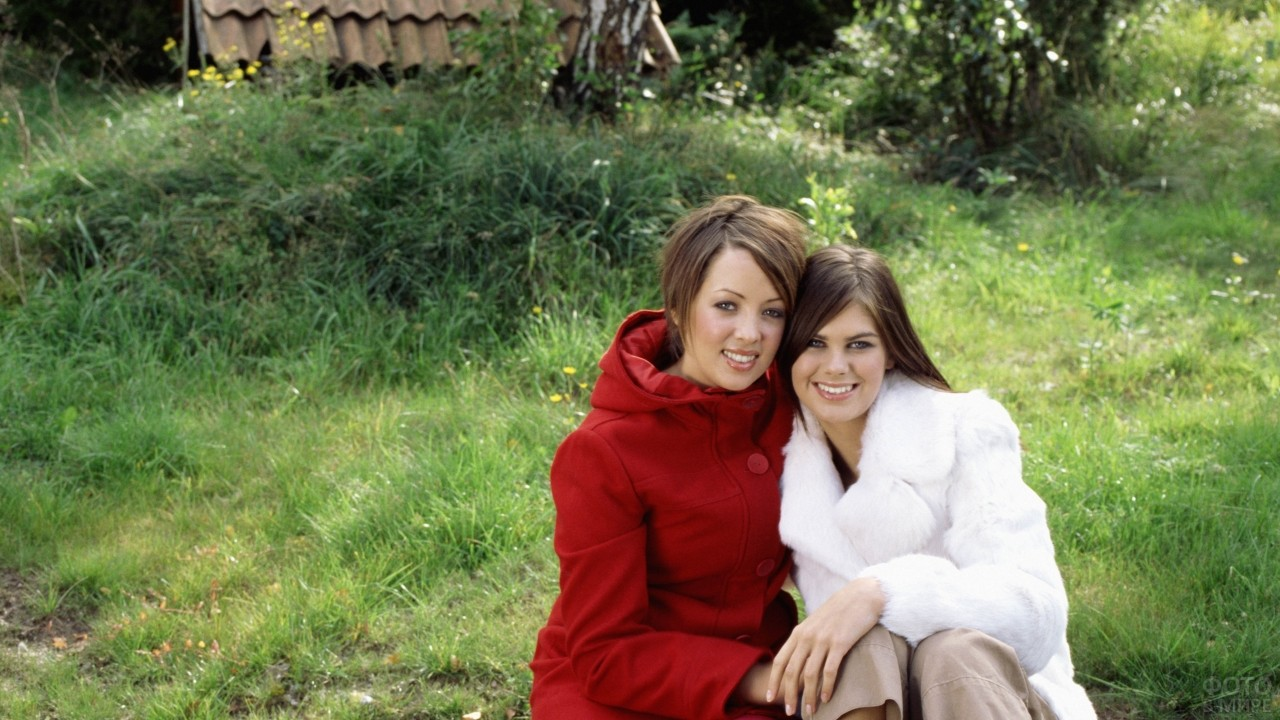 Деревенские подруги сидят на траве
