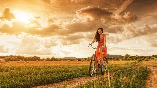 Девушка едет на велосипеде по просёлочной дороге