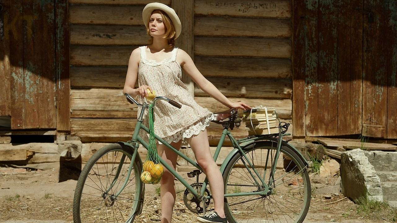 Девушка на велосипеде с апельсинами в авоське