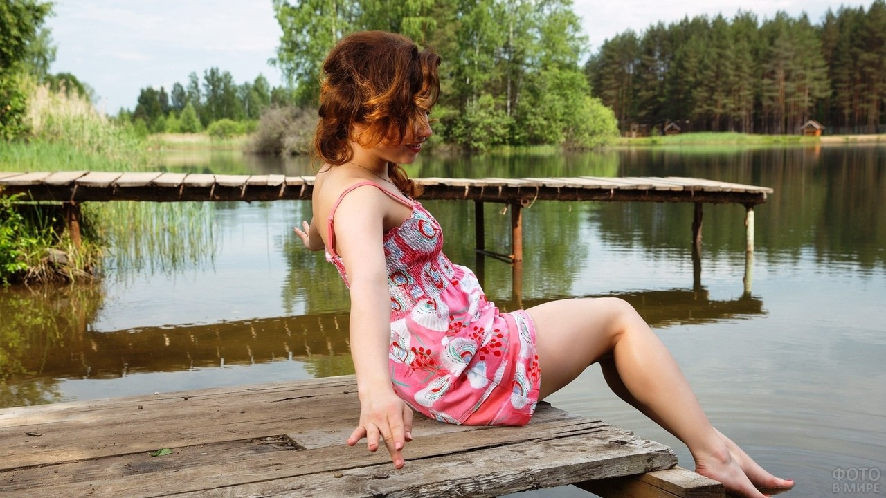Девушка опускает ноги в воду