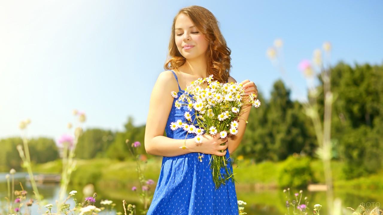 Девушка в синем платье с букетом ромашек